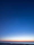 与星的夜空在海滩 蓝色展望期少校编号安排了行星空间范围视图 免版税库存照片