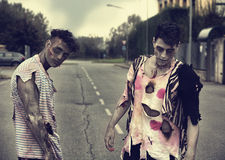 站立在空的城市街道的两个男性蛇神 图库摄影