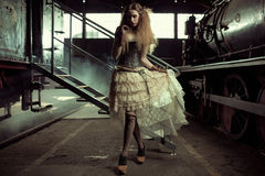年轻人打扮了空的火车站的妇女 库存图片