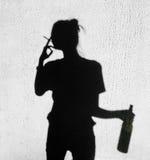 抽烟在墙壁背景的妇女的阴影 免版税库存照片