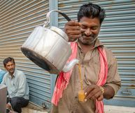 人倾吐杯子热的牛奶茶印地安人样式 免版税库存图片