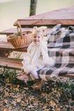 坐在湖附近的小女孩佩带的雨披在秋天森林里 免版税库存照片