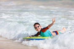 在识别不明飞机委员会的男孩游泳 图库摄影