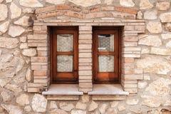有两个小窗口的老石墙在木制框架 免版税图库摄影