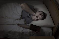 成熟人不安定在床上,当设法睡觉时 免版税图库摄影