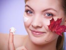 应用关心皮肤透明油漆 少妇女孩的面孔有红槭叶子的 免版税库存照片