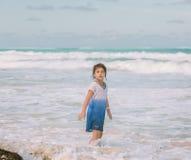 走在大西洋的儿童女孩在海滩附近在晴朗的温暖的天 免版税图库摄影