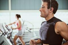 健身房:人听到音乐,当跑步在踏车时 免版税库存照片