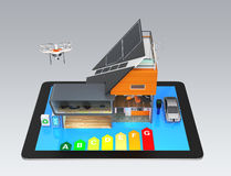 一台片剂个人计算机的聪明的房子在灰色背景,与能量规定值图 库存图片