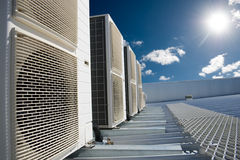 与太阳和蓝天的空调器单位 免版税库存图片