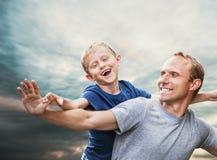 在蓝天的愉快的微笑的儿子和父亲画象 免版税库存图片