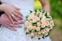 拿着桃红色和白玫瑰的婚礼花束新娘 免版税库存图片