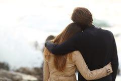 拥抱在冬天的夫妇的后面看法 免版税库存照片