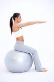性感的适合妇女坐大锻炼球 免版税库存图片