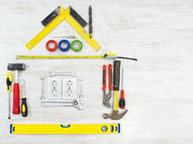 Εργαλεία με μορφή του σπιτιού, σπίτι πέρα από το ξύλινο άσπρο υπόβαθρο Στοκ φωτογραφίες με δικαίωμα ελεύθερης χρήσης