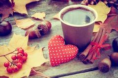 温暖的咖啡杯、红色心脏和秋天静物画 免版税库存照片