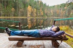 休息在湖附近的男性远足者在秋天森林里 库存照片