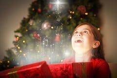 打开一件不可思议的圣诞节礼物的小女孩的综合图象 免版税库存照片