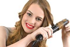使用陶瓷头发直挺器的妇女 免版税库存照片