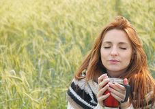 享受热的饮料的美丽的妇女在秋天寒冷天 免版税图库摄影