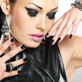 美好的有黑钉子的时尚性感的妇女在俏丽的面孔 免版税库存照片