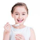 吃酸奶的一个小女孩的画象 免版税库存照片