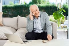 在老人院的老人回答的智能手机 免版税图库摄影