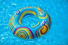 在蓝色游泳水池的五颜六色的水池浮游物 免版税库存图片