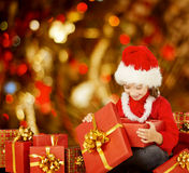 Подарочная коробка ребенк рождества раскрывая присутствующая, счастливый ребенок в шляпе Санты Стоковые Изображения RF