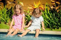 坐在游泳池附近的兄弟和姐妹 库存照片