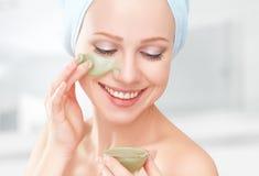 美丽的面部护肤的女孩在卫生间里和面具 免版税图库摄影