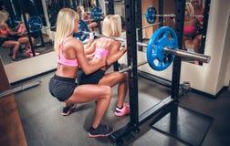 做与杠铃的健身房的性感的妇女蹲坐 免版税图库摄影