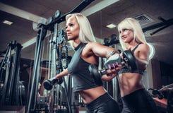 做与哑铃的健身妇女锻炼在健身房 免版税图库摄影