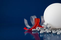 白色、银和红色圣诞节装饰品在深蓝背景 免版税库存照片