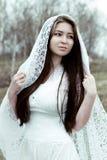 白色礼服的美丽的无辜的妇女 免版税库存图片