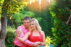 拍照片的富感情的年轻夫妇使用一个巧妙的电话 免版税库存图片