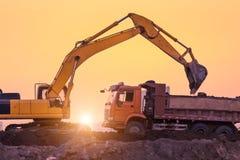 运转在日落的重的轮子挖掘机机器 免版税图库摄影