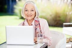 使用膝上型计算机的资深妇女在老人院门廊 免版税库存图片