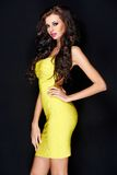 黄色礼服的肉欲的相当长的头发妇女 免版税库存照片