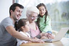 使用膝上型计算机的愉快的三一代家庭在桌上在房子里 免版税库存图片