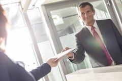 Επιχειρηματίας που λαμβάνει το έγγραφο από το ρεσεψιονίστ στην αρχή Στοκ εικόνα με δικαίωμα ελεύθερης χρήσης