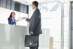 Επιχειρηματίας που λαμβάνει το έγγραφο από το ρεσεψιονίστ στην αρχή Στοκ Εικόνα