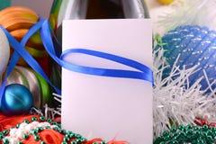 与酒瓶珍珠和空的纸笔记的圣诞卡 免版税库存照片