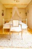 卧室内部 机盖床和减速火箭的椅子 免版税图库摄影