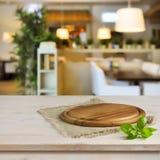 在桌上的切板在被弄脏的餐馆内部背景 免版税库存图片