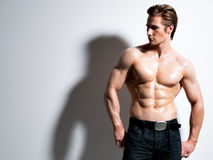 摆在演播室的英俊的肌肉年轻人 免版税库存照片