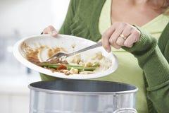 妇女刮的食物残羹剩饭到垃圾桶里 库存图片