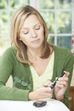 Женщина проверяя уровень сахара в крови дома Стоковая Фотография