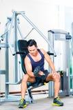 亚裔在健身房的人举的手重量 库存图片