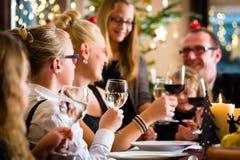 庆祝圣诞晚餐的家庭 免版税库存图片